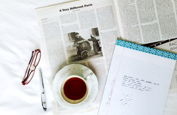 book review gear: glasses, pen, notebook, tea, and New York Review of Books
